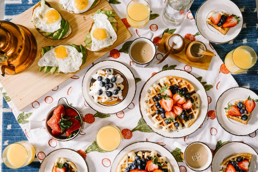 Brunch spread mimosas coffee waffles fruit avocado toast eggs
