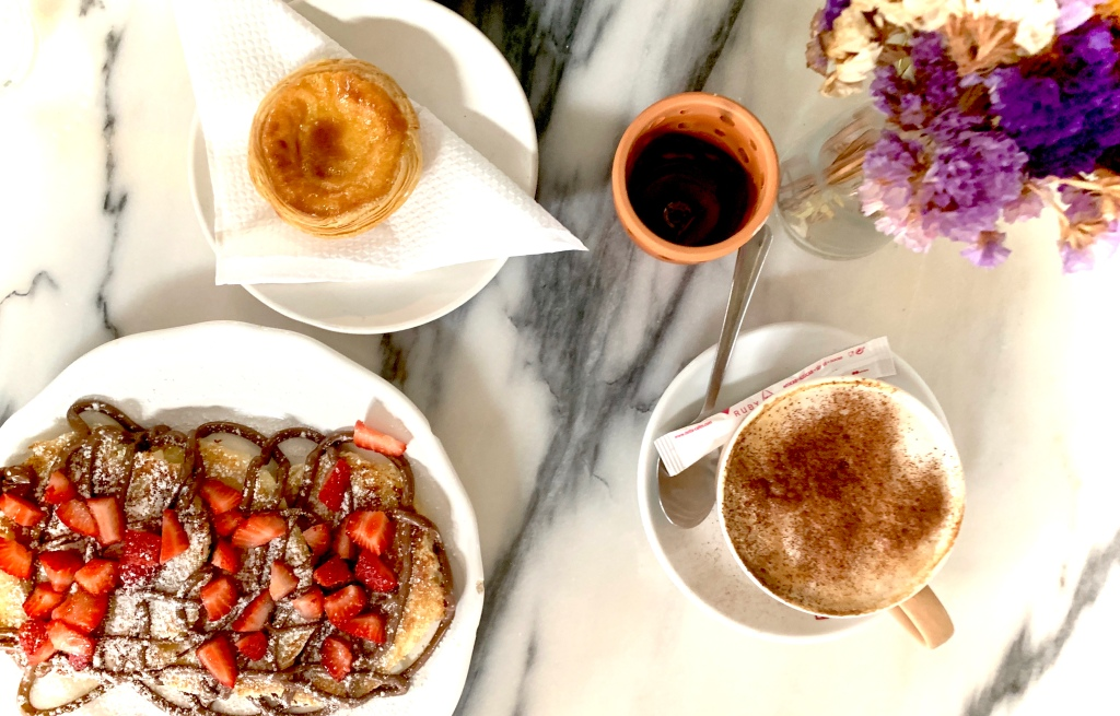 Nutella and Strawberry pancakes, pastel de Nata a custard tart, and a cappuccino